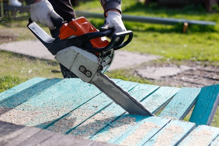 Man sawing boards with a chainsaw. Close up.