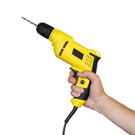 Hand holding a yellow electric drill. Close up. Isolated on white background.