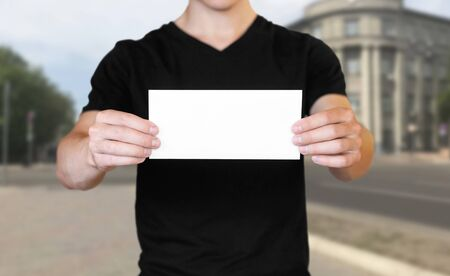 A man holding a white sheet of paper. Holding a booklet. Close up. The background of the city.