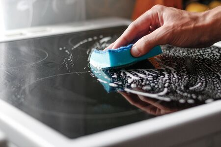Hand washes the hob with a sponge and foam. Close up. Foto de archivo