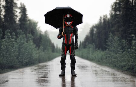 Motorcyclist in full gear and helmet with umbrella in the rain. Motorcyclist in the dark woods. Zdjęcie Seryjne