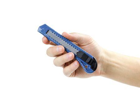 Main tenant un couteau de papeterie bleu. Fermer. Isolé sur fond blanc. Banque d'images