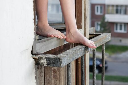A man stands in an open window. The man wants to jump out of the window. Feet are on the window. Suicide. Stock fotó