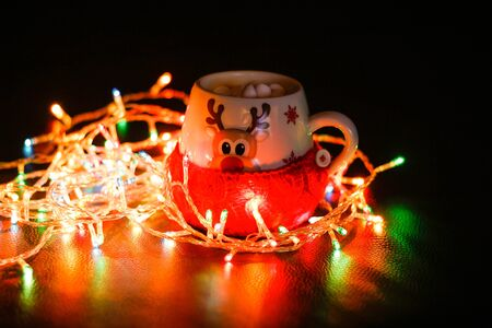 The mug is wrapped in a wool sock. A mug of cocoa and marshmallows, a garland lit next to it. Lights in the dark. Stock fotó