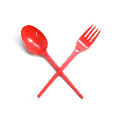 Plastic red disposable spoon and fork crossed. Close up. Isolated on white background. Stock Photo