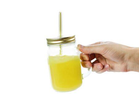 Hand holding glass jar mug with orange juice. Close up. Isolated on white background.