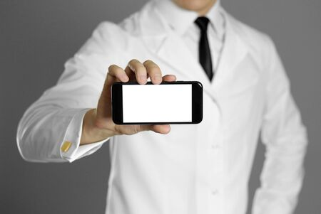 A doctor in a white shirt and black tie holds a smartphone. Without a face. Stockfoto