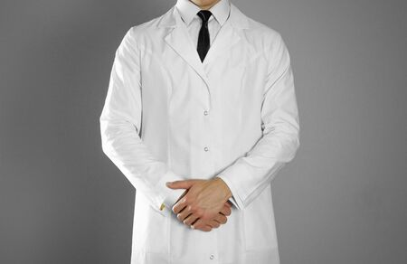 A man in a white coat, white shirt and black tie.