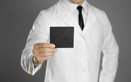 Doctor. A man in a white coat, white shirt and black tie holds a black business card. Without a face. Stockfoto