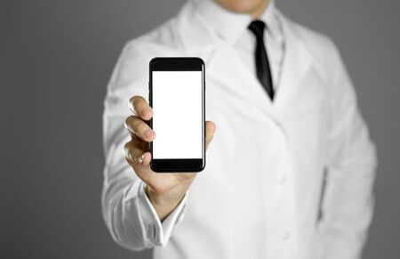 A doctor in a white shirt and black tie holds a smartphone. Stockfoto