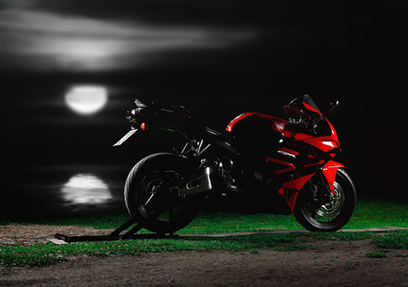 KRASNOYARSK, RUSSIA - May 27, 2019: Red and black sportbike Honda CBR 600 RR 2005 PC37 near the river at night. The moon shines on the river.