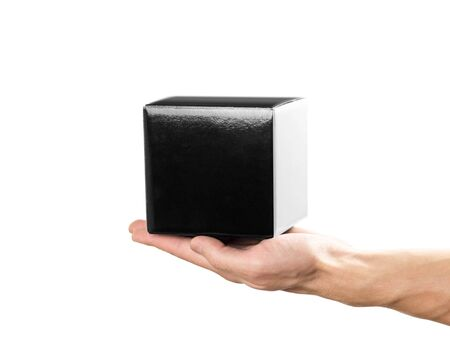 Hand holds a small black box. Close up. Isolated on white background.