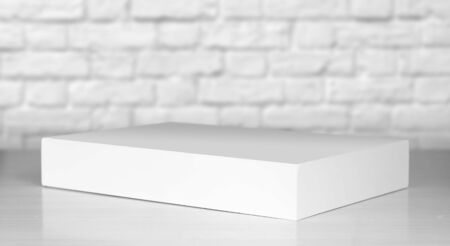 A white laptop box sits on a wooden table. Close up.