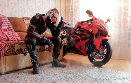 KRASNOYARSK, RUSSIA - October 7, 2019: Beautiful motorcyclist in full gear and helmet on a red and black Honda 2005 CBR 600 RR (PC37) in house.