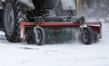 Tractor cleans the sidewalks of snow. Snow removal equipment. Stock fotó