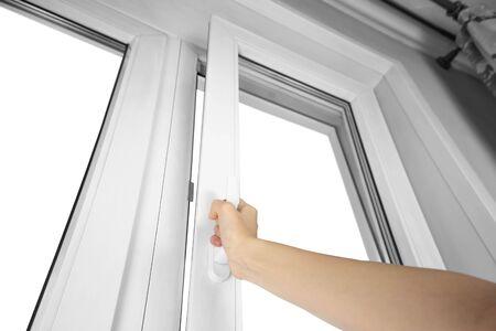 La mano abre el plástico blanco de la ventana. De cerca. Foto de archivo