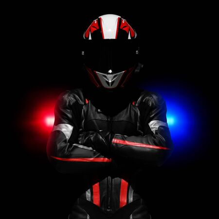 Beautiful motorcyclist in a leather suit, helmet with a black visor. Motorcyclist in the dark. Behind him, the red and blue lights of a police car.