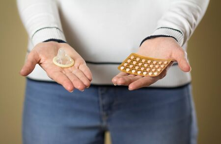 The girl holds a condom and birth control pills. Close up.