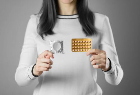 The girl holds a condom and birth control pills. Close up. Isolated on grey background. Stock fotó