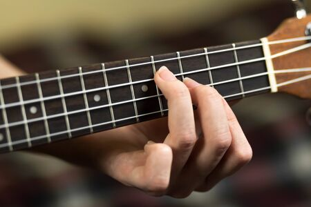 Hand holding a chord on the ukulele. Close up. Isolated on white background. Stock fotó