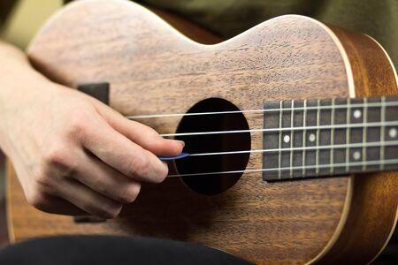 Girl playing the ukulele. Close up. Isolated on white background.
