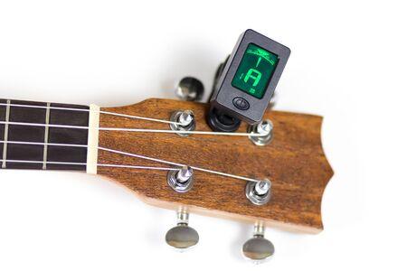 Tuning ukulele tuner. Close up. Isolated on white background.