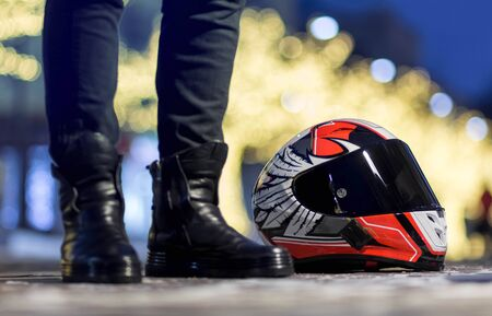 Beautiful red motorcycle helmet with black visor. Lies on a bright garland. Stock fotó