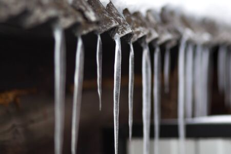 Icicles hang on the old roof. Close up.