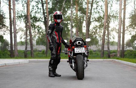KRASNOYARSK, RUSSIA - June 11, 2019: Beautiful motorcyclist in full gear and helmet on a red and black Honda 2005 CBR 600 RR (PC37).