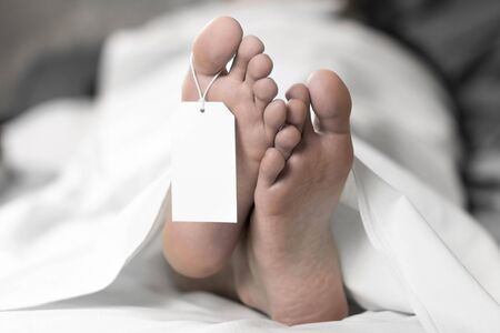 A dead man is lying in the morgue. Tag on the leg. Close up. Stock Photo