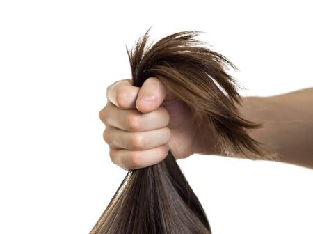 A mans hand pulls a womans hair. Close up. Isolated on a white background.