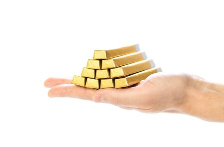 The hand holds chocolate bars in the shape of gold bars. Close up. Isolated on a white background.