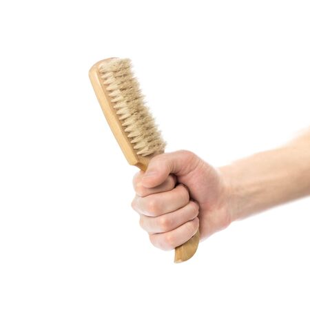 Hand holding a brush with a wooden handle. Close up. Isolated on a white background.