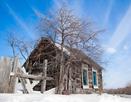 Old abandoned house with a tree. Blue sky. Winter.