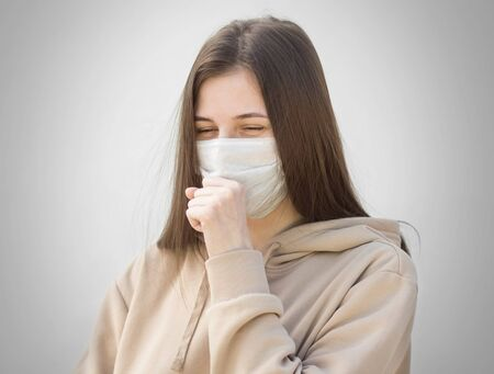 The girl in the medical mask coughs. Close up. Isolated on a grey background.