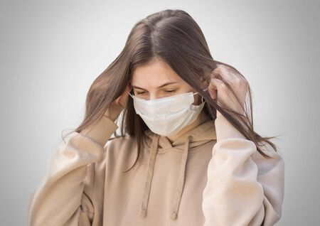 The girl puts on a medical mask. Close up. Isolated on a grey background.