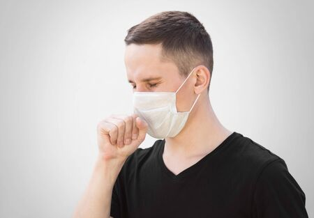 A man in a medical mask coughs. Close up. Isolated on a grey background. Stock Photo