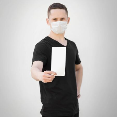 A man in a medical mask holds a blank white sheet of paper. Close up. Isolated on a grey background.