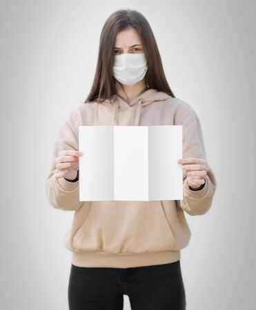 A girl in a medical mask holds an empty white sheet of paper. Close up. Isolated on a grey background.