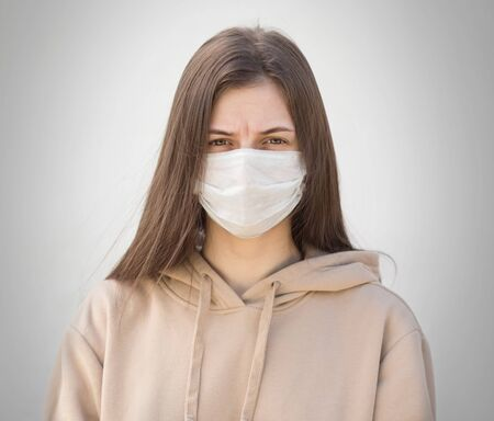 The girl in the medical mask. Close up. Isolated on a grey background.