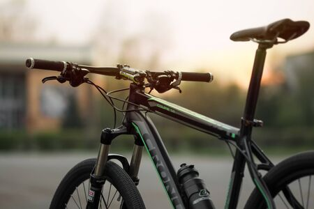 KRASNOYARSK, RUSSIA - April 29, 2020: Beautiful black and green mountain bike in the city. Evening. Close up.