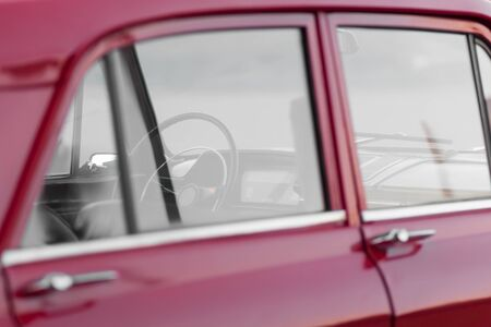 Interior of a red retro car. Transparent windows, thin steering wheel.