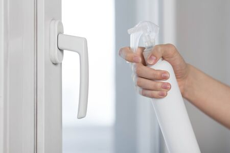 Disinfection of the handle of a plastic white window. Close up.