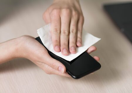 Disinfection of the black smartphone. Cleaning of the screen. Close up.
