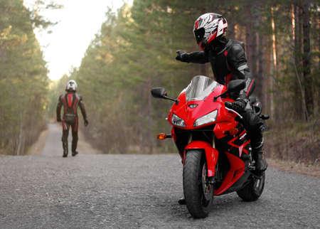 KRASNOYARSK, RUSSIA - May 3, 2019: Beautiful motorcyclist in full gear and helmet on a red and black Honda 2005 CBR 600 RR (PC37).