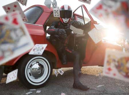 A man in a helmet and motorcycle gear throws playing cards at the camera.