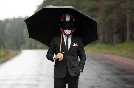 A man in a classic black suit and a helmet under an umbrella.