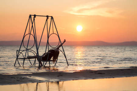 Girl on a swing in the sea. At sunset.