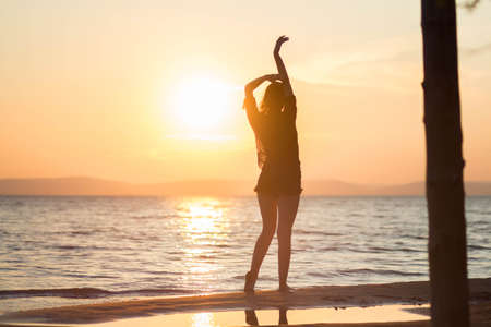Beautiful dancing girl on the beach during sunset.