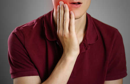 Guy touches a hand over the aching tooth. Toothache. Closeup. The lesion is highlighted in red